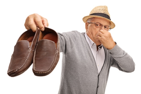 Man Holding Smelly Shoes