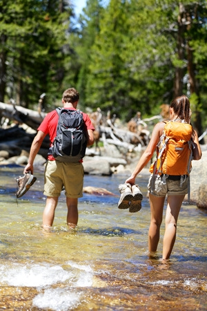 Couple Crossing A Stream With Hiking Boots in the Hand