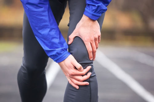 Man Clucthing Knne in Pain While Running