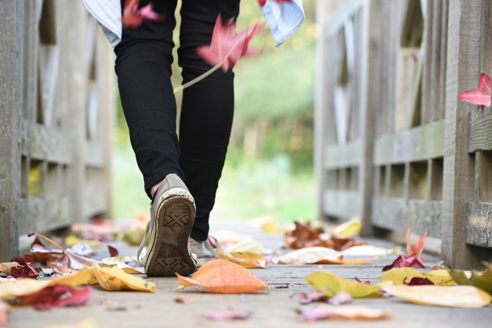 Woman Walking Through Fallen Leaves