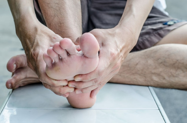 Man Massaging Top of his Foot
