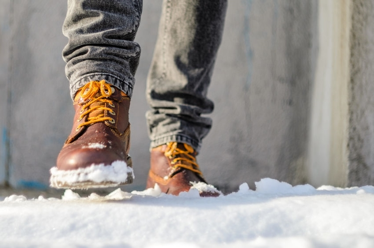 Man With Work Boots Walking in the Snow