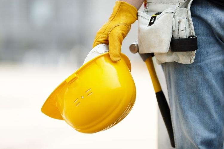 Construction Worker Weraing Tool Belt and Holding Hard Hat