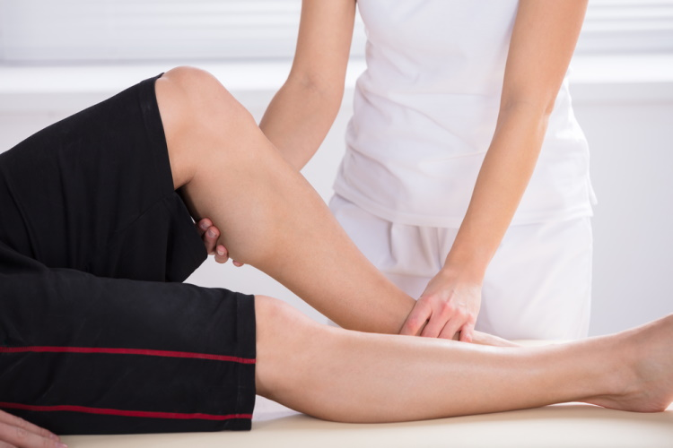 physiotherapist giving knee therapy